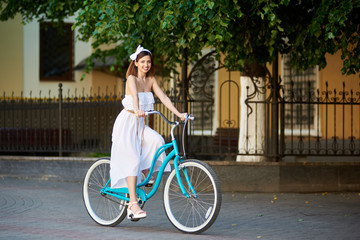 Smiling pretty girl in a white dress is riding a vintage blue bicycle down a city street with a metal fence and green trees on the background. Turquoise bike beautiful woman lady bow happiness joy.