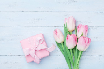 Pink tulip flowers and gift or present box on blue wooden table top view. Greeting card for Womans or Mothers Day. Flat lay.
