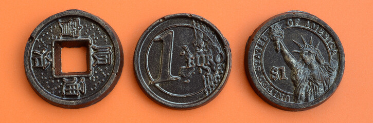 Three chocolate products in the form of Euro, USA and Japan coins lie on an orange plastic background. A model of cash coins in an edible form