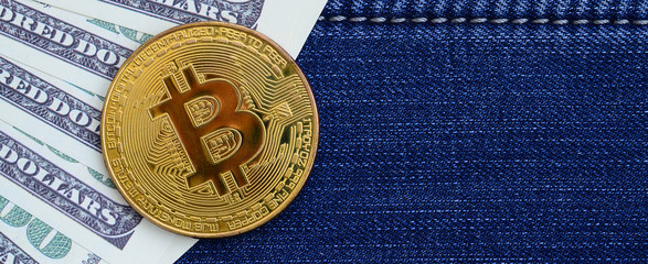 Golden Bitcoin and dollar bills lies on a blue jeans fabric. New virtual money. New crypto currency in the form of the coins