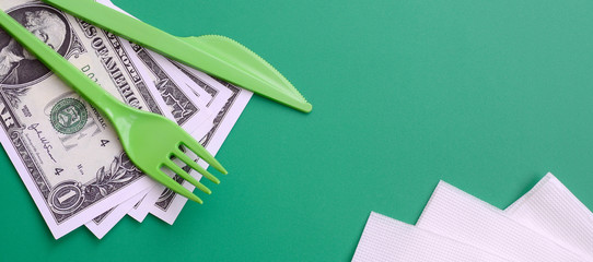 Disposable plastic cutlery green. Plastic fork and knife lie on a small amount of US dollars next to napkins