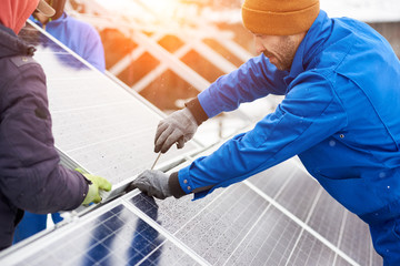 Worker with tools maintaining photovoltaic panels in winter. Engineers installing solar panels.