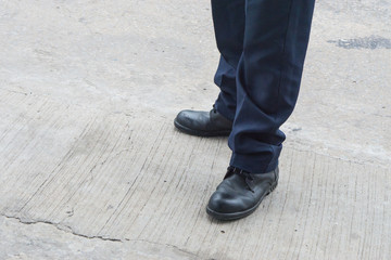 Leg of man with long black trousers standing on the street., business men shoes stand on walking street