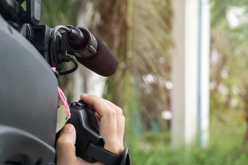 Covering an event with a video camera., Videographer takes video camera with free copy space for your text.