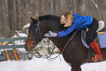 A young girl with white hair is riding a horse. The girl hugs her favorite horse. Winter cloudy day.