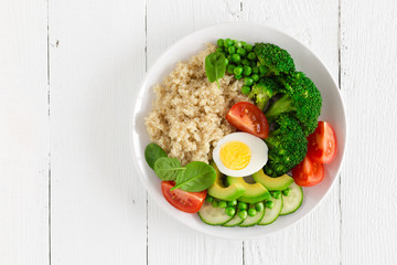 Healthy detox dish with egg, avocado, quinoa, spinach, fresh tomato, green peas and broccoli on white wooden background, top view