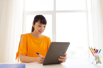 asian student girl with tablet pc learning at home