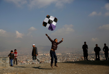 An Afghan boy launches a kite as he plays on top of a hill in Kabul