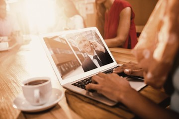 Composite image of businesswoman working on laptop at office