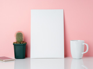 Blank white frame and plant cactus, cup of coffee or tea on a white table against the pink wall with copy space. Mockup with copy space.