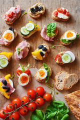 Top view of assorted sandwiches with baguette bread, cheese, ham, eggs, hummus and veggies. Healthy snack on wooden table.