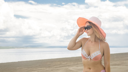 Attractive woman in a hat stands on the beach against the blue sea. She has sunglasses and a panama on her head. On her body is a swimsuit and a silk cape. In the background are very beautiful deep