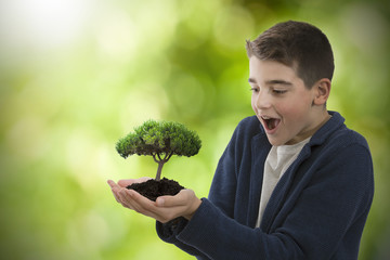 child surprised with the young tree in the hands