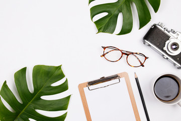Frame made of tropical palm leaf, vintage camera, glasses, coffee cup and clipboard on white background. Flat lay, top view woman blog mockup. summer travel concept.