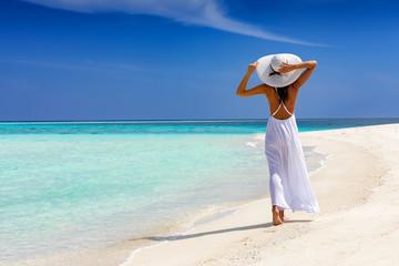 Elegante Frau in weiß läuft über einen tropischen Strand und genießt ihren Urlaub
