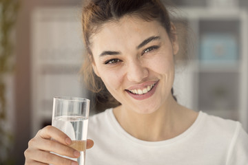 Smiling young woman holding glass of water look,