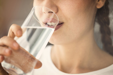 Young woman drinking glass of water close up view
