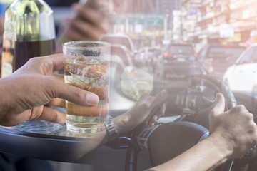 Concept Drunk Driving : Drinking, Hand hold mix alcohol and car steering wheel. Double exposure