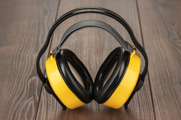 hearing protection yellow ear muffs on wooden table