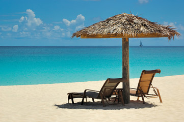 Straw parasol with cozy chaise lounge at white sand tropical beach with the view over the Caribbean Sea, in Anguilla, British overseas territory