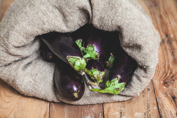 few eggplants are seen in sack on wooden boards