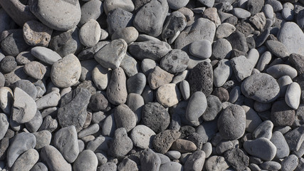 Grey smooth pebble beach background with copy space, conceptual texture from nature
