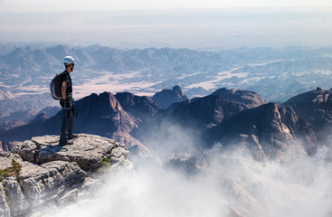 Mountain climber standing on summit with vast view