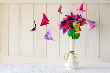 Origami paper flowers in vase and butterflies on white wooden wall. Paper art craft