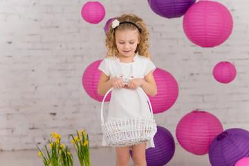 Cute little girl holds easter eggs basket