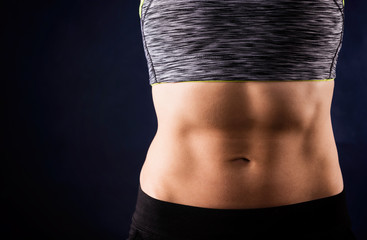 Woman`s flat stomach with press. ABS. Sport style. Isolated on dark blue background. Workout concept.