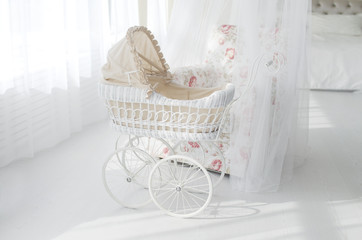 white stroller for a baby in a white classic interior