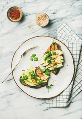 Healthy vegan breakfast or lunch. Flat-lay of avocado toast with seasoning and glass of lemon water over marble background, top view. Clean eating, detox, weight loss, dieting food concept
