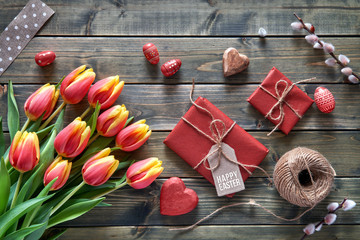 Easter arrangement: red tulips, wrapped gifts, cord and decorative hearts on wooden tabke, flat lay