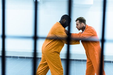 side view of multiethnic prisoners fighting behind prison bars