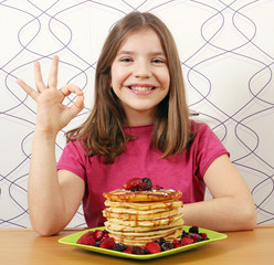 happy little girl with panckaces dessert and ok hand sign