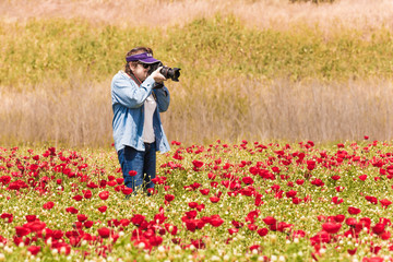 Elderly woman taking pictures of field with flowers