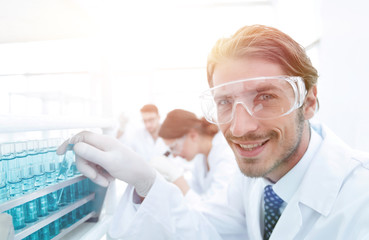 close-up of a happy male scientist wearing safety glasses
