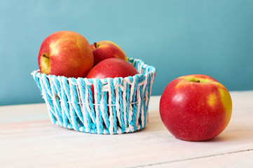 Red apples in a basket on a white wooden background