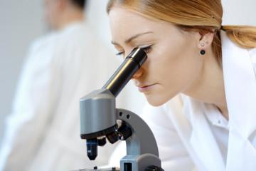 Arzt oder Wissenschaftler bei Untersuchung und Auswertung mit Mikroskop