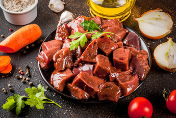 Sliced raw beef liver with spices, herbs and vegetables, dark rusty table copy space