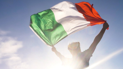 Young man holding italian national flag to the sky with two hands at the beach at sunset italy