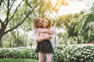 Portrait of Young Happy Beautiful Mother and Daughter Hugging. Embrace in Sunny Day on Meadow