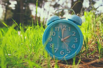 Image of spring Time Change. Summer back concept. Vintage alarm Clock outdoors.