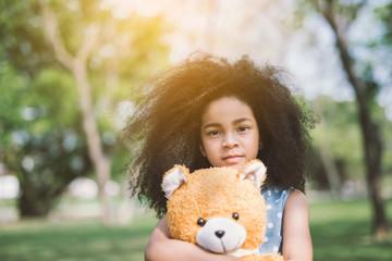 Little cute african american girl hugging embraces an amusing teddy bear against summer nature.