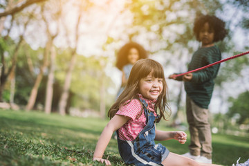 summer, childhood, leisure and people concept - group of happy kids playing with friend on green field outdoors