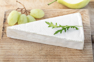 Fresh Brie Cheese  on cutting board with grapes and fruits, top view. Brie Cheese  on white  rustic wooden background. Camembert cheese. .