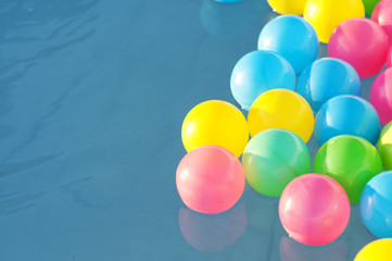 Multicolored plastic balls float in the children's pool