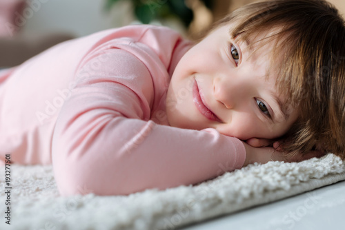 Smiling child girl with down syndrome lying on soft floor