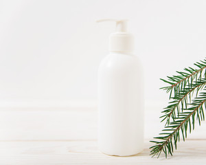 White cosmetic bottle with fir-tree.wooden background.mokup for design