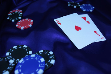 Poker table during a game. Casino, gambling, poker, people and entertainment concept - close up of poker player with chips at purple casino table